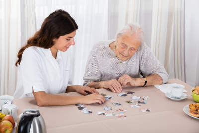 caregiver and elder playing puzzle